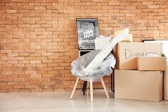 Carton boxes and interior items in room. Moving house concept royalty free stock photography