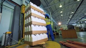 Carton boxes with plastic containers are getting stacked by male loader. 4K stock footage