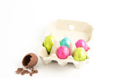 Carton of easter eggs with one broken on surface Royalty Free Stock Photos