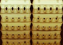Carton egg boxes on a  black reflective surface Royalty Free Stock Image