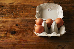 Carton of eggs on a wooden table Stock Photos