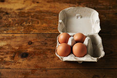 Carton of eggs on a wooden table Royalty Free Stock Photos