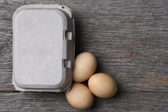 Carton of fresh eggs with three on the rustic wood table. Royalty Free Stock Images