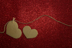 Carton heart attached to the rope on red shining background Royalty Free Stock Images