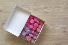 Carton paper present box with colorful macaroons cakes on wooden stock photo