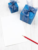 Carton with pencil in front of  blue gift boxes Stock Image