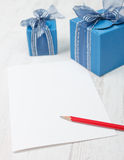 Carton with pencil in front of gift boxes Royalty Free Stock Photo