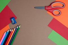 Cartone variopinto, matite e forbici rosse Immagine Stock