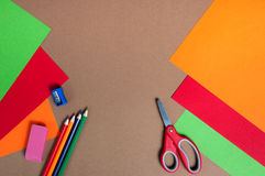 Cartone variopinto, matite e forbici rosse Fotografia Stock