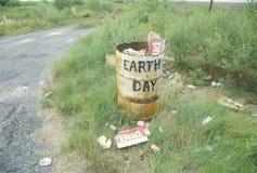 Cartones de la cerveza de la cartulina en la tierra al lado de un bote de basura con el ?Earth Day? de las palabras pintado en su Fotografía de archivo libre de regalías