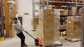 Cartoni commoventi di un lavoratore con il carrello elevatore a forcale in magazzino/deposito industriale Concetto del trasporto video d archivio
