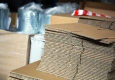 Cartoni spiegati per le scatole nel magazzino Immagine Stock