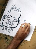 Man drawing caricature. Male artist drawing a caricature cartoon with black marker on white paper Royalty Free Stock Photo
