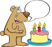 Cartoon bear with a speech balloon and a birthday cake. Stock Image