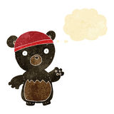 Cartoon black bear wearing hat with thought bubble Stock Photo