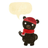 Cartoon black bear in winter hat and scarf with speech bubble Stock Images