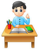 Cartoon boy learning at table giving thumbs up Stock Photo