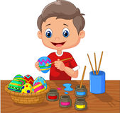 Cartoon boy painting Easter eggs Royalty Free Stock Images