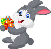 Cartoon bunny holding decorated egg Stock Images