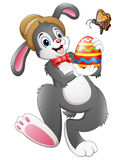 Cartoon bunny holding Easter egg with butterfly Stock Photos
