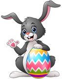 Cartoon bunny waving hand with holding Easter egg Stock Photo