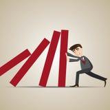 Cartoon businessman resist dominos falling Stock Image