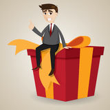 Cartoon businessman sitting on big gift box Royalty Free Stock Photos