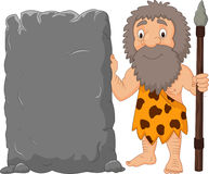 Cartoon caveman holding stone sign Stock Photo