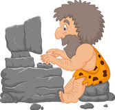 Cartoon caveman using a stone computer Stock Image