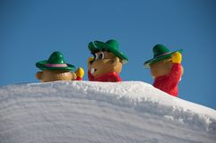 Cartoon characters on snow covered roof. Cartoon characters on the top of a roof, nearly covered by snow, in a ski report in the Tirol, Austria royalty free stock image