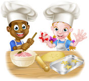 Cartoon Child Chefs Baking Cakes. Cartoon boy and girl kids, one black one white, dressed as chefs or bakers baking cakes and cookies in chef hats royalty free illustration