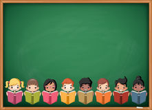 Cartoon children reading books over green chalkboard blackboard. Royalty Free Stock Photo