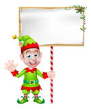 Cartoon Christmas Elf Sign. Cartoon Christmas Elf or Santa Christmas helper holding a blank sign Stock Photos