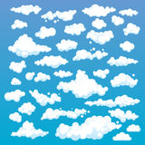 Cartoon Clouds Set On Blue Sky Background. Set of funny cartoon clouds, smoke patterns and fog icons, for filling your sky scenes Royalty Free Stock Photo