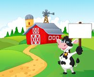 Cartoon cow holding blank sign with farm background Royalty Free Stock Image