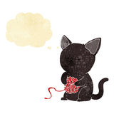cartoon cute black cat playing with ball of yarn with thought bu Stock Images