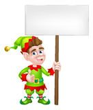 Cartoon Elf Sign. Cartoon Christmas Elf or one of Santa s Christmas helpers holding a sign and giving a thumbs up Royalty Free Stock Images
