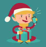 Cartoon Elf Talking on the Phone and Holding a Present Royalty Free Stock Photography