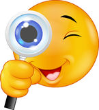 Cartoon Emoticon holding a magnifying glass Stock Photos