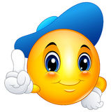 Cartoon emoticon smiley wearing a cap and pointing Royalty Free Stock Image
