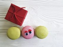 Cartoon eyes tasty macaron on a wooden box. Cartoon eyes macaron on a wooden box tasty Royalty Free Stock Images