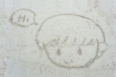 Cartoon face of little boy drawn on the sand Royalty Free Stock Images