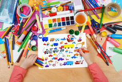 Cartoon game toy and people collection child drawing , top view hands with pencil painting picture on paper, artwork workplace Royalty Free Stock Image