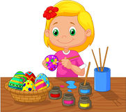 Cartoon girl painting Easter eggs Stock Photography