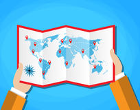 Cartoon hands hold folded paper map of world with color point markers. World map countries. vector illustration in flat. Design on blue background Stock Image