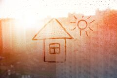 Hand drawn house and sun drawn by child s hand on window with raindrops on sunset