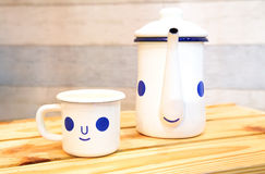Cartoon kettle and coffee cup with a happy smile on wood table. Royalty Free Stock Image