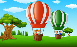 Cartoon kids inside a hot air balloon flying over a green park Royalty Free Stock Photography