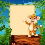 Cartoon leopard presenting on hollow log near the empty framed signboard Stock Photo