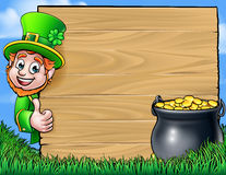 Cartoon Leprechaun St Patricks Day Background Sign. A Cartoon Leprechaun character leaning around a wooden sign and giving thumbs up with a pot of gold. St Stock Image